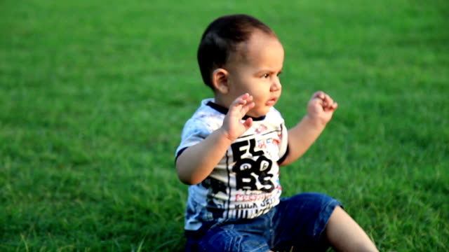Baby boy playing in the park during sunset