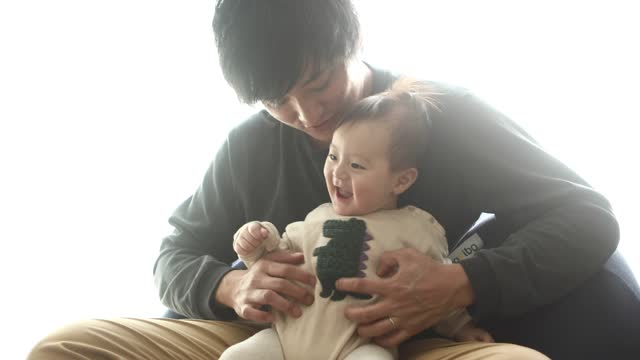 a baby boy playing on his father's lap - genderblend stock videos & royalty-free footage