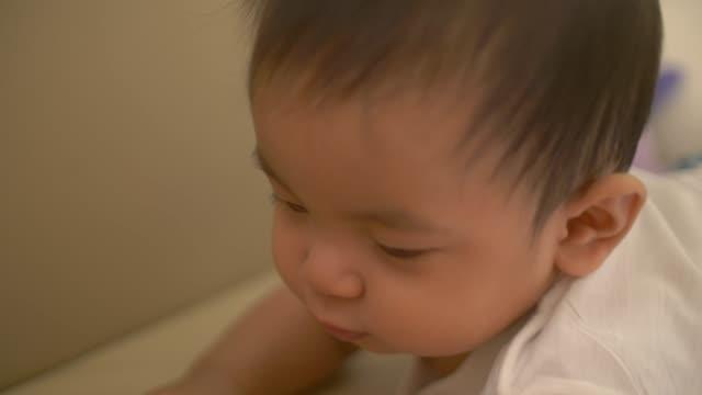 vídeos de stock e filmes b-roll de baby boy playing on sofa - vida de bebé