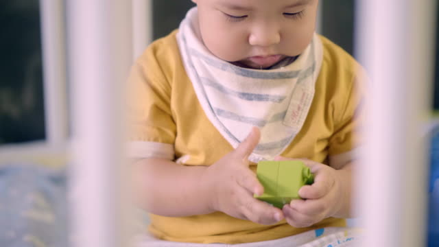baby boy playing toy in his crib - soltanto un neonato maschio video stock e b–roll