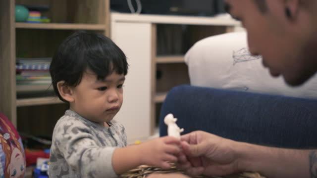 vidéos et rushes de petit garçon jouant jouet avec père - genderblend