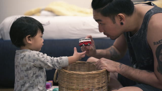 baby boy playing toy with father - genderblend stock videos & royalty-free footage