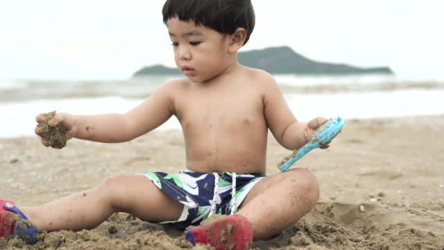 baby boy playing toy with sand on the beach - one baby boy only stock videos & royalty-free footage