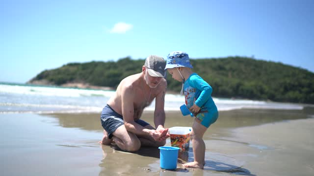 vidéos et rushes de bébé jouant le seau de whit et la pelle à la plage avec son grand-père - 2 3 ans