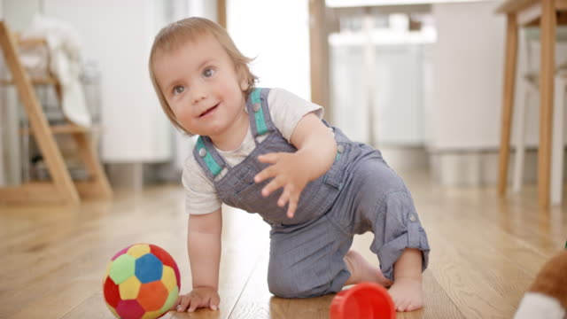 slo mo baby boy playing with a soft ball and falling down while tying to grab it - part of a series stock videos & royalty-free footage