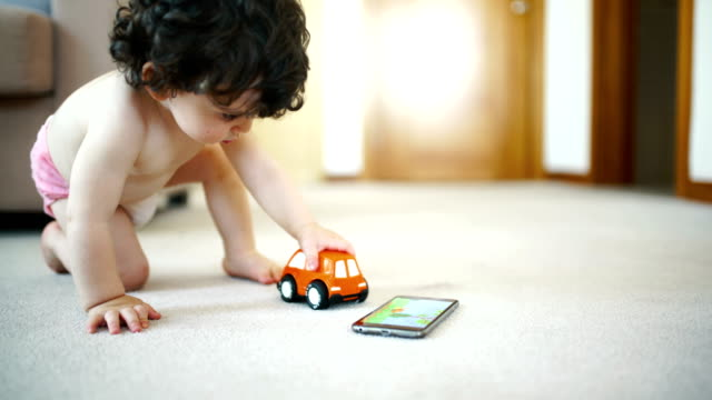 Baby boy playing with a toy car.