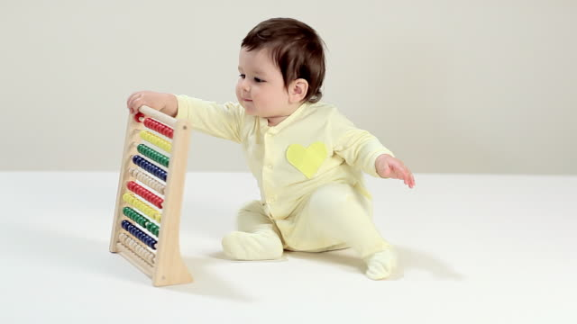 baby boy playing with abacus - tutina video stock e b–roll