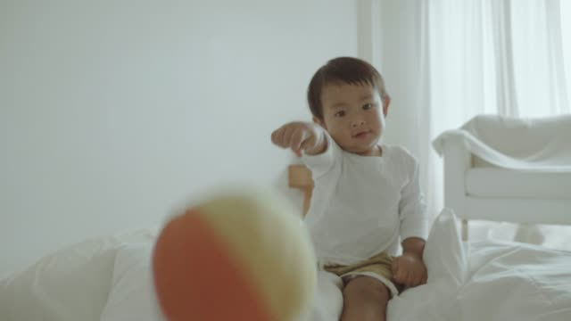 Baby boy playing with ball at home.