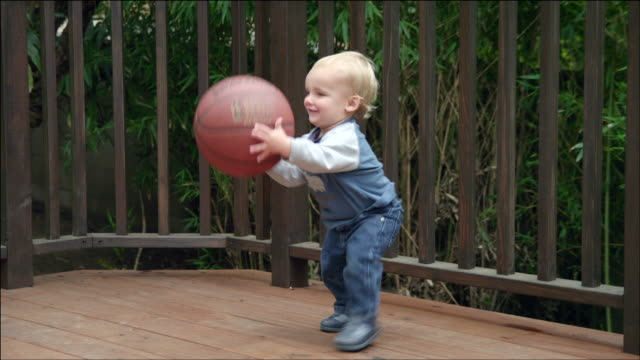 WS TD Baby boy playing with basketball on garden deck / Los Angeles, CA, United States