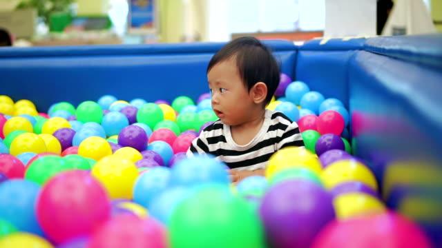 vídeos de stock e filmes b-roll de baby boy playing with colorful ball. - 6 11 meses