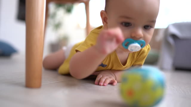 baby boy playing with his favorite toy on floor - reaching stock videos & royalty-free footage