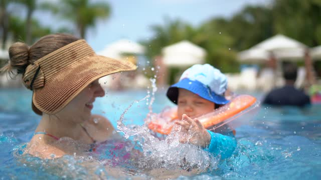 baby boy playing with his mother in a swimming pool - tourist resort stock videos & royalty-free footage