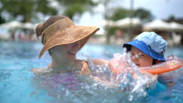 vídeos de stock, filmes e b-roll de menino brincando com a mãe em uma piscina - estação turística