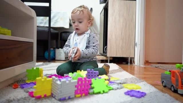 vídeos de stock e filmes b-roll de baby boy playing with plastic blocks on the floor - quebra cabeças