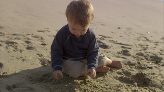 slo mo ms baby boy playing with sand on beach / vista del mar, california, usa - one baby boy only stock videos & royalty-free footage