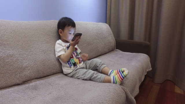 stockvideo's en b-roll-footage met baby boy playing with smart phone - one baby boy only