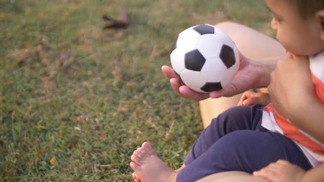 vídeos de stock, filmes e b-roll de bebê menino brincando com bola de futebol - muito pequeno