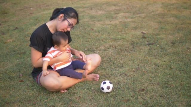 baby jungen spielen mit einem fußball-ball - männliches baby stock-videos und b-roll-filmmaterial