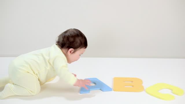 baby boy playing with toy alphabet blocks - tutina video stock e b–roll