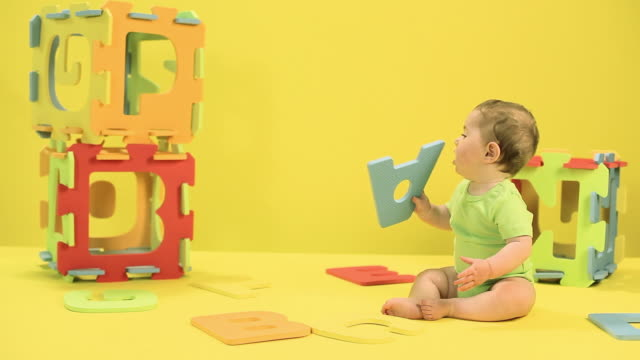 baby boy playing with toy alphabet letters - tutina video stock e b–roll