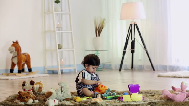 Baby boy playing with toys in the home