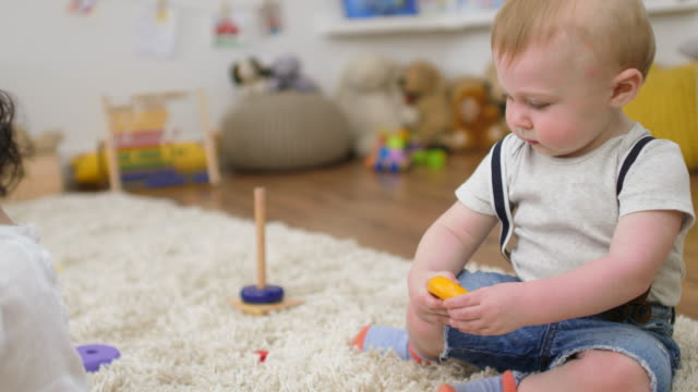 baby boy playing with wooden disc in nursery - nursery school building stock videos and b-roll footage