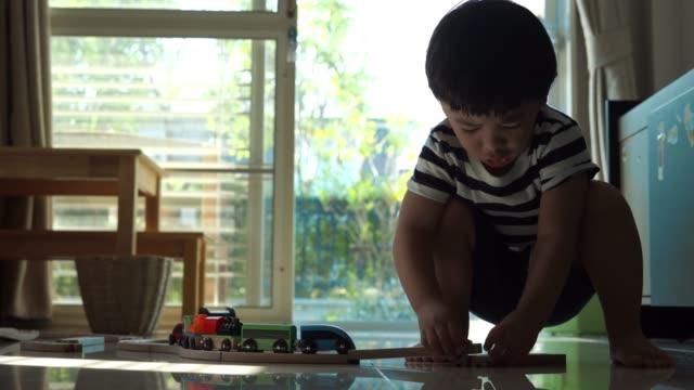 自宅で木製の電車をプレイする男の子 - 線路点の映像素材/bロール