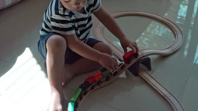 自宅で木製の電車をプレイする男の子 - railway track点の映像素材/bロール