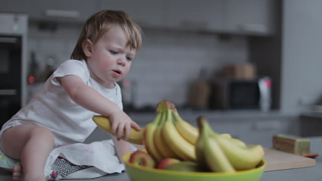 baby boy plays with bananas in the fruit bowl - fruit bowl stock videos & royalty-free footage