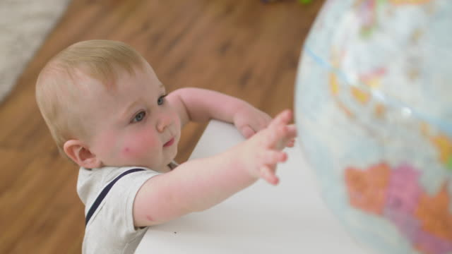 baby boy reaching for globe on table top - babies only stock videos & royalty-free footage