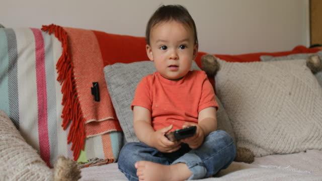 テレビを見る準備ができて男の子 - テレビのリモコン点の映像素材/bロール