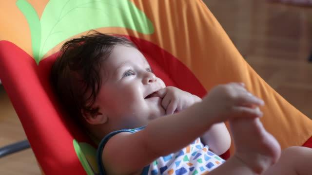 vídeos de stock, filmes e b-roll de bebé que relaxa e que tem o divertimento no assento do bebê - olhos azuis