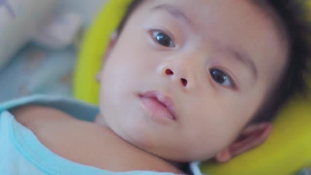 baby junge entspannen auf dem bett - menschliche gliedmaßen stock-videos und b-roll-filmmaterial