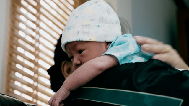 baby boy rests on the shoulder of his asian grandmother - wishing well stock videos & royalty-free footage