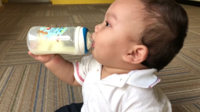 baby boy siiting and bottle feeding milk - one baby girl only stock videos & royalty-free footage