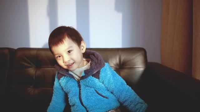baby boy singing on the sofa with smile at home - ein männliches baby allein stock-videos und b-roll-filmmaterial