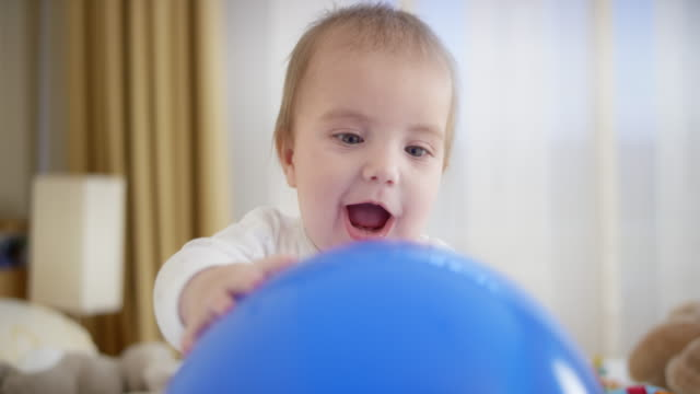 baby boy sitting and playing with large blue balloon - part of a series stock videos & royalty-free footage