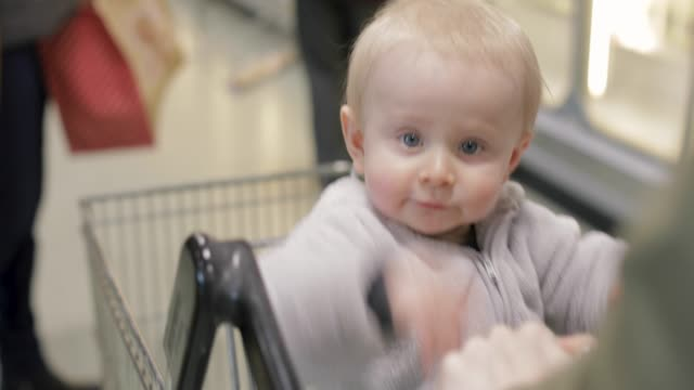 baby boy sitting in a shopping cart seat - trolley stock videos and b-roll footage