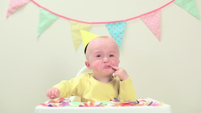 baby boy sitting in highchair with bunting - tutina video stock e b–roll