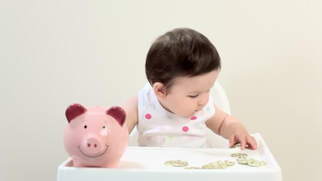 baby boy sitting in highchair with piggy bank - ein männliches baby allein stock-videos und b-roll-filmmaterial