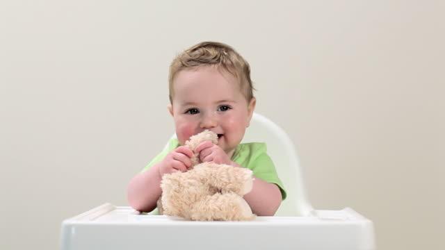 vídeos de stock, filmes e b-roll de baby boy sitting in highchair with teddy bear - cadeirinha cadeira