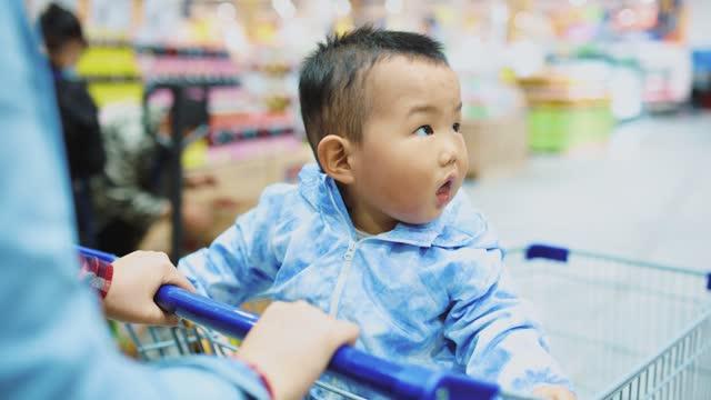 baby junge sitzt in einkaufswagen in einem supermarkt - ein männliches baby allein stock-videos und b-roll-filmmaterial