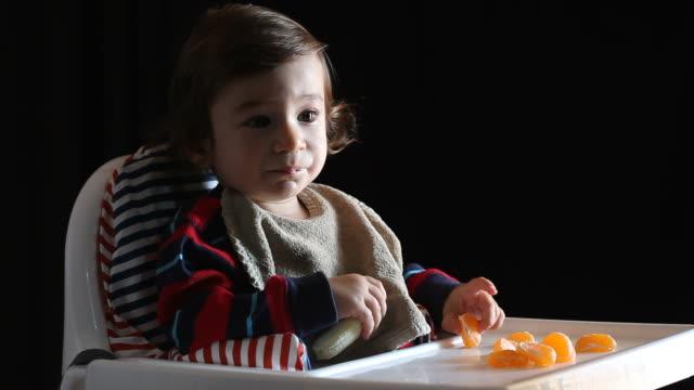 vídeos de stock e filmes b-roll de bebé sentado na cadeira alta e comer frutas - bebés meninos