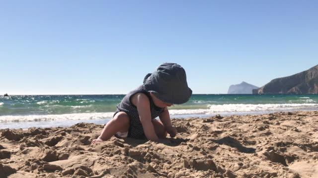 pojke sitter på stranden på sommaren - endast en pojkbaby bildbanksvideor och videomaterial från bakom kulisserna