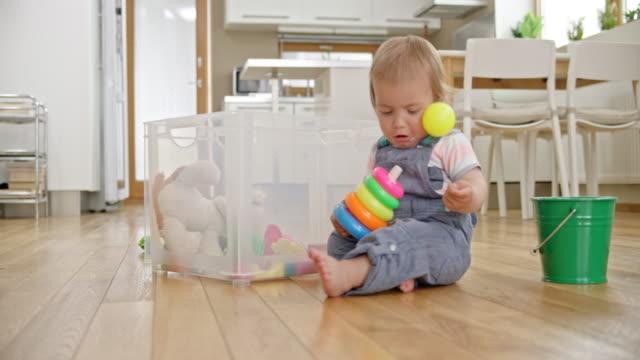 床に座って、カラフルなおもちゃで遊ぶ男の子の SLO MO 赤ちゃん