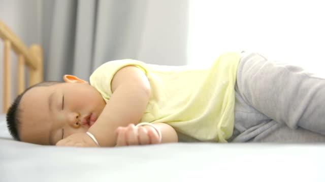 寝室で眠っている男の子の赤ちゃん - 男の赤ちゃん一人点の映像素材/bロール