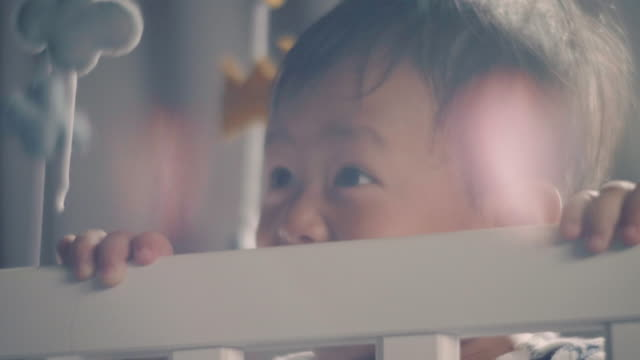 Baby boy standing and laughing in crib at home.