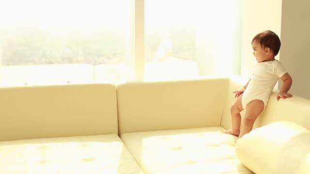 baby boy standing on sofa  - ein männliches baby allein stock-videos und b-roll-filmmaterial