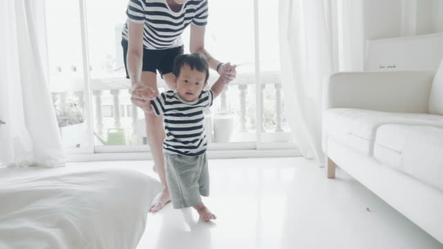 baby boy (6-11 months) taking first steps - primi passi video stock e b–roll