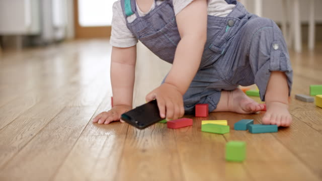 slo mo baby boy throwing a mobile phone on the floor - lanciare video stock e b–roll